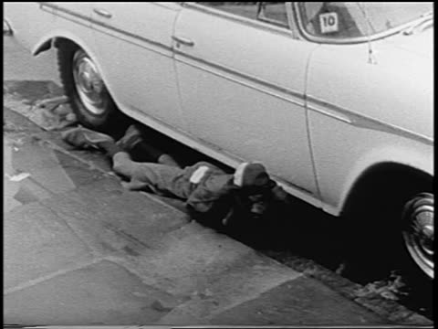 man lying by car on street to escape gunfire during newark riots, new jersey / newsreel - 1967 bildbanksvideor och videomaterial från bakom kulisserna