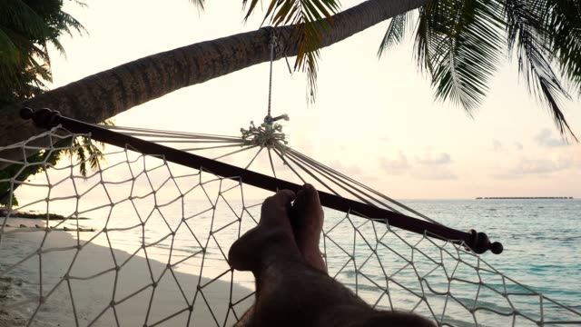 man lying down on a hammock in a paradisiac beach at maldives - tourist resort stock videos & royalty-free footage