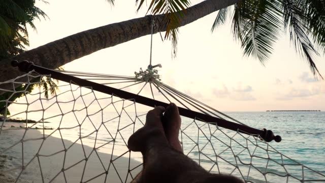 stockvideo's en b-roll-footage met man liggen op een hangmat in een paradijselijke strand op de malediven - verblijfsoord