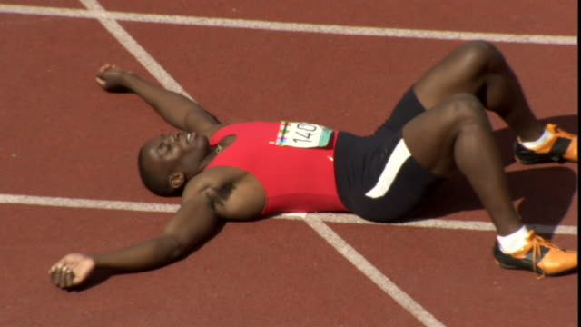 ha ms zo man lying down on track after winning race/ sheffield, england - finishing stock videos & royalty-free footage