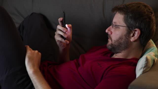vídeos de stock, filmes e b-roll de homem deitado trabalhando no celular - sala de estar