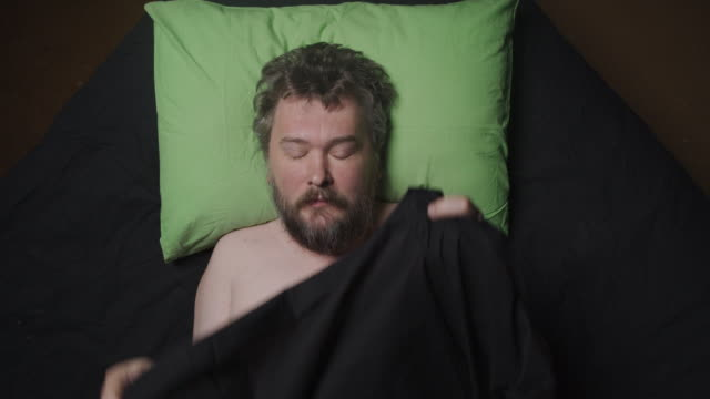man lying in bed and taking the blanket off - pillow stock videos & royalty-free footage