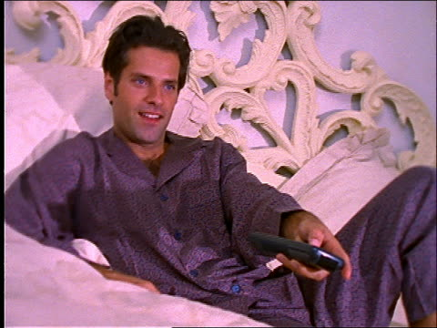 Man lying in bed holding remote control