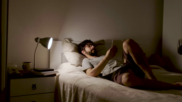 man lying in bed reading book - bedroom stock videos & royalty-free footage