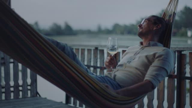 mann liegt in hängematte und trinkt wein - faulheit stock-videos und b-roll-filmmaterial