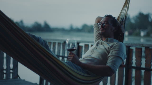 man lying in hammock and drinking wine - lakeshore stock videos & royalty-free footage