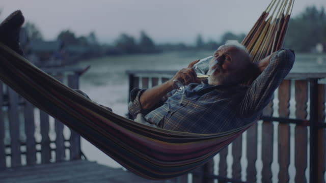 vídeos de stock e filmes b-roll de man lying in hammock and drinking wine - cama de rede