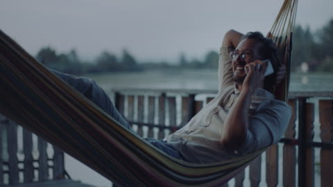 man lying in hammock and talking on the phone - leisure activity stock videos & royalty-free footage