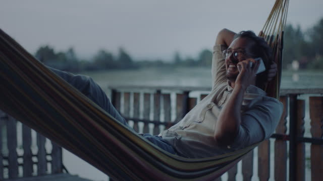 man lying in hammock and talking on the phone - riposarsi video stock e b–roll