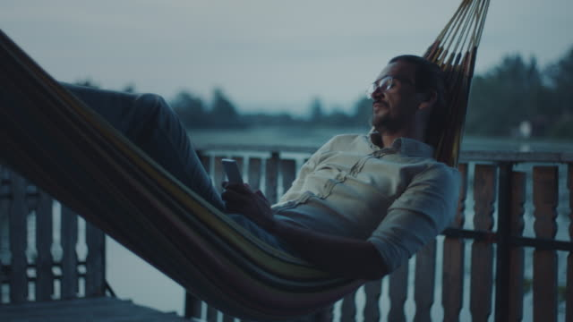 man lying in hammock and texting - reclining stock videos & royalty-free footage