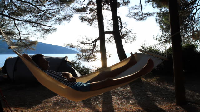 hd: man lying in hammock on the beach - lying on back stock videos & royalty-free footage