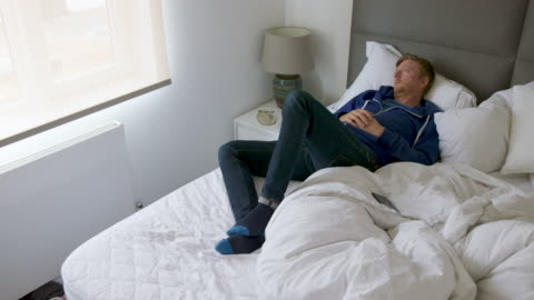 man lying on bed. he looks lost in thought - lying down stock videos & royalty-free footage