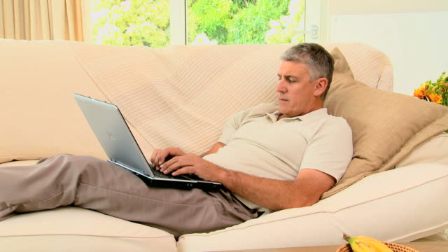 man lying on coch working on his laptop / cape town, western cape, south africa - only mature men stock videos & royalty-free footage