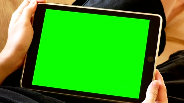 man lying on couch and holding digital tablet computer with green screen for chroma key