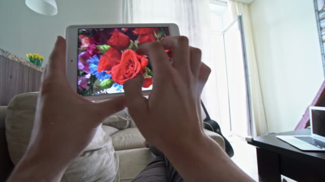 pov of man lying on couch and watching photos with flowers on tablet - bouquet stock videos and b-roll footage
