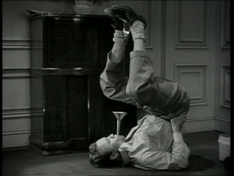 b/w 1946 man lying on floor holds bottle in raised feet, dripping water into funnel in mouth - hiccup stock videos and b-roll footage