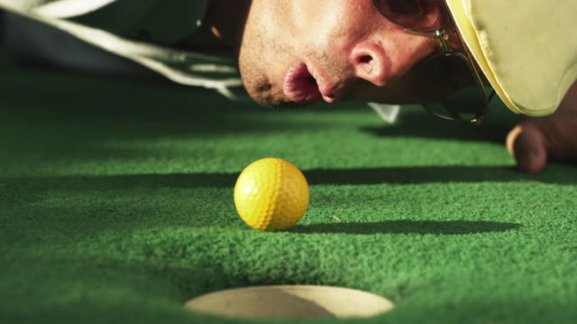 cu man lying on golf course green blowing golf ball towards hole / orem, utah, usa - 失敗点の映像素材/bロール