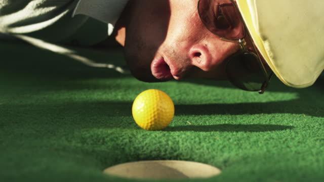 cu man lying on golf course green blowing golf ball towards hole / orem, utah, usa - deception stock videos and b-roll footage