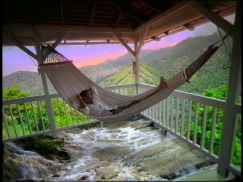 composite man lying on hammock on porch overlooking hills with streams under hammock / jamaica - jamaican people stock videos and b-roll footage