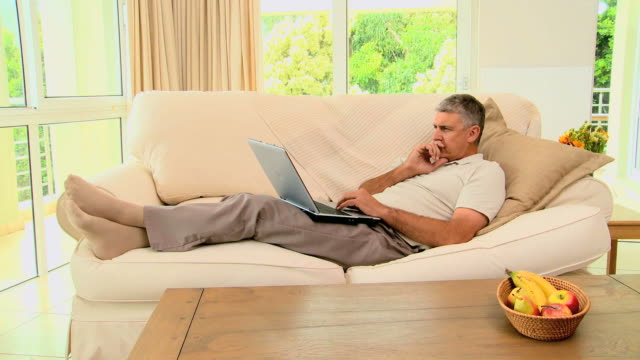 Man lying on sofa excited about something on laptop / Cape Town, Western Cape, South Africa