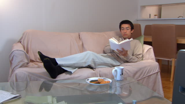 MS, Man lying on sofa, reading book