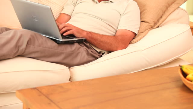 Man lying on sofa using laptop / Cape Town, Western Cape, South Africa