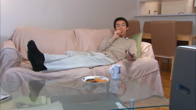 MS, Man lying on sofa, watching television