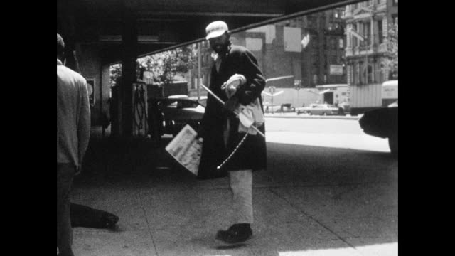 Man lying on the sidewalk by a garage as two men stand over him on the corner of 3rd and the Bowery