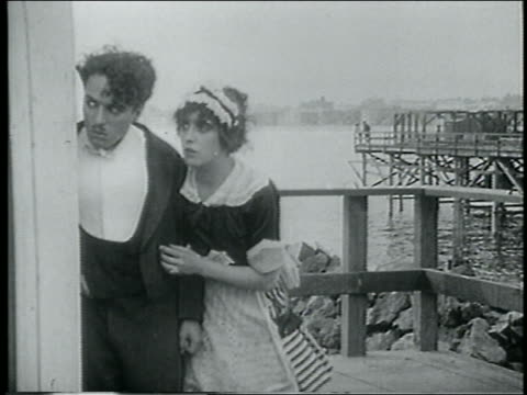 stockvideo's en b-roll-footage met b/w 1915 man maid on pier watching something offscreen / feature - 1915