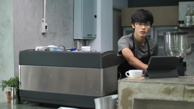 男はカフェでデジタル タブレットで注文からコーヒーを作る - 整える点の映像素材/bロール