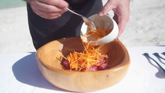 a man makes a poke salad lunch with ahi tuna and carrots in a bowl. - territori francesi d'oltremare video stock e b–roll