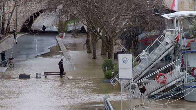 man makes a walkway with a bench and other objects so he can reach his barge as the docks under the quays of the hôtel de ville are inundated by... - four objects stock videos & royalty-free footage
