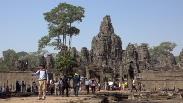 Man makes selfie with giant stone face tower of Bayon temple