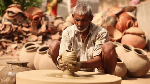 man making a earthen pot on a pottery wheel, faridabad, haryana, india - one mature man only stock videos & royalty-free footage