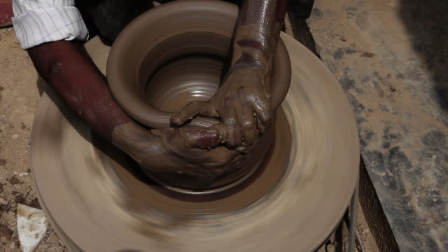 man making a earthen pot on a pottery wheel  - pottery stock videos & royalty-free footage