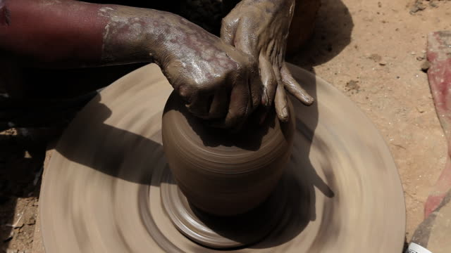 man making a earthen pot on a pottery wheel  - potter's wheel stock videos & royalty-free footage