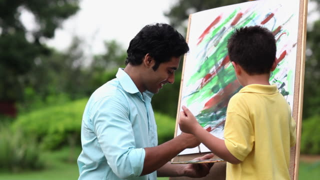 man making a painting with his son on an easel - easel stock videos and b-roll footage