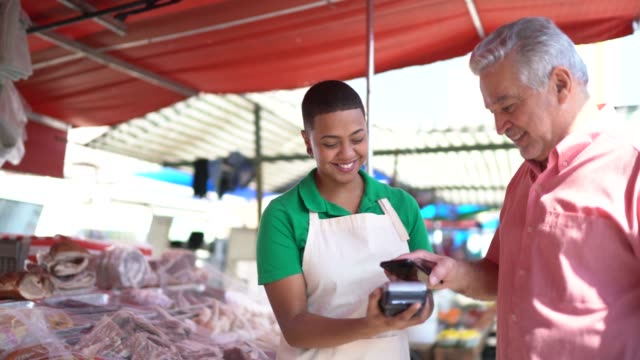 man making a payment using credit card in a street market - retail occupation stock videos & royalty-free footage