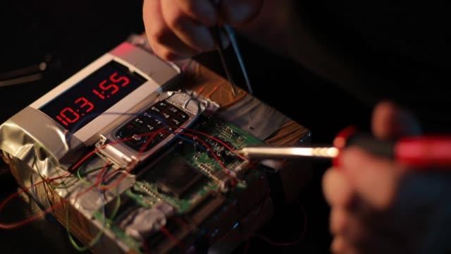 stockvideo's en b-roll-footage met man het maken van een tijdbom in de workshop - bomb countdown timer
