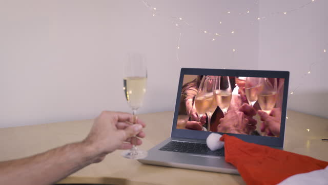 Man making a toast on a video call while celebrating christmas