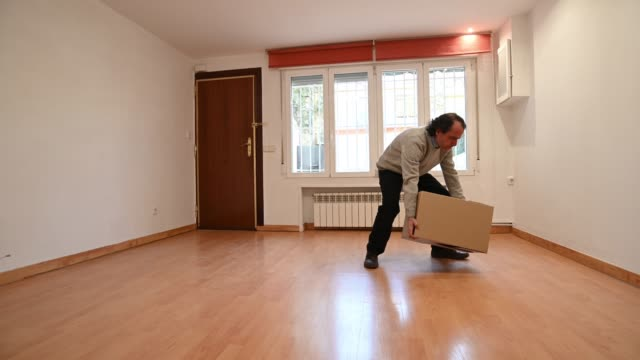 man making an effort when lifting very heavy cardboard box in an empty living room of a house - schwer stock-videos und b-roll-filmmaterial