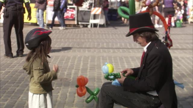ms man making balloon animals on street, girl standing beside and talking / portland, oregon, usa - portland oregon点の映像素材/bロール