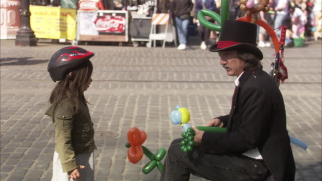 ms man making balloon animals on street, girl standing beside and talking / portland, oregon, usa - magician stock videos & royalty-free footage