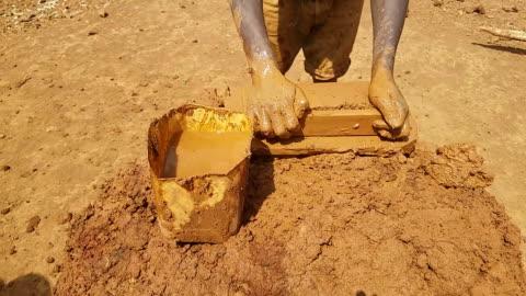 vídeos y material grabado en eventos de stock de hombre haciendo ladrillos en forma de moda antigua en áfrica - ladrillo