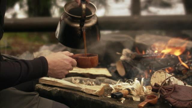 a man making coffee over a camp fire sweden. - bricco per il caffè video stock e b–roll