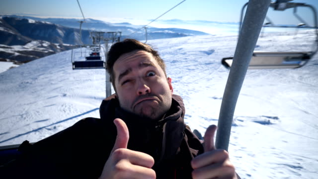 Man making funny faces on ski lift
