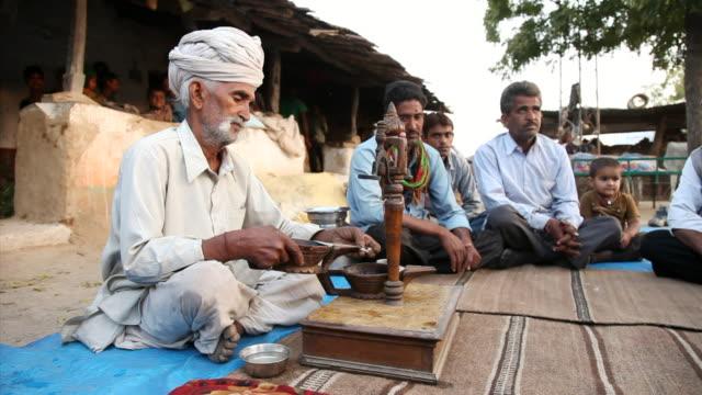 ms man making opium tea / rajasthan, india - feierliche veranstaltung stock-videos und b-roll-filmmaterial