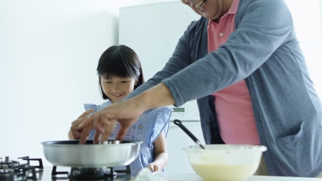 Man Making Pancakes With Granddaughter