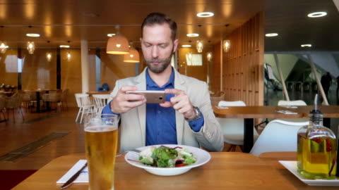 mann macht bilder von nahrungsmitteln für instagram - stock video - image stock-videos und b-roll-filmmaterial