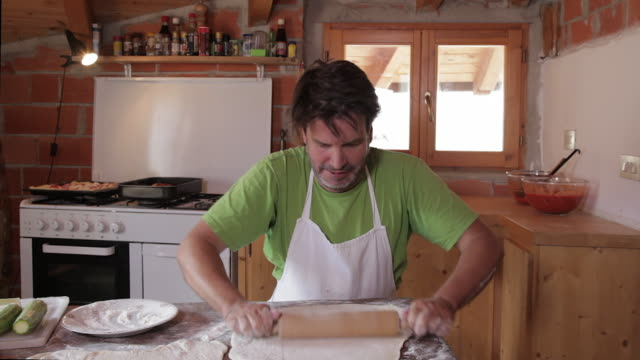 man making pizzas in kitchen of home